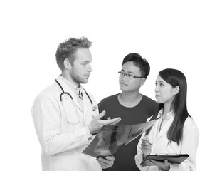 Male doctor with assistant explaining health condition to the pa