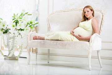 Pregnant woman lying on couch at home