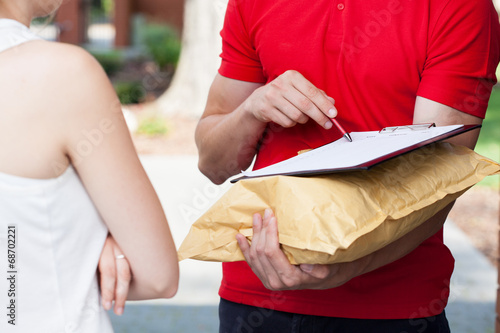 canvas print picture Delivery man asking for a signature