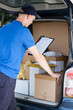 canvas print picture - Courier and a car full of packages