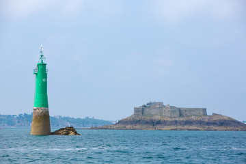Private house and green lighthouse in the bay of Saint-Malo