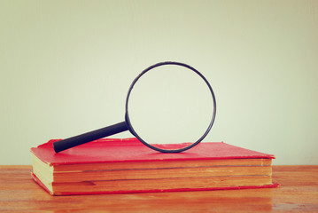 old book and magnifying glass. room for text. image is retro fil
