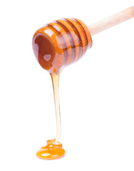 Honey dripping from wooden dipper