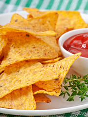 Nachos and tomato dip decorated with thyme leaves
