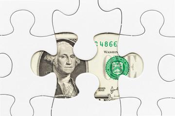 US dollar banknote hidden under puzzle financial concept