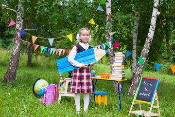 Happy schoolgirl child kid girl holding a huge big pencil