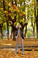 Happy little girl playing with autumn foliage in a park