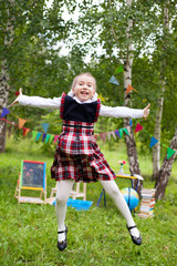 Happy schoolgirl child kid girl jumping and smiling