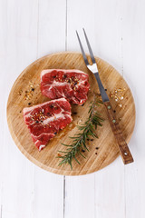 Red meat and rosemary over white background