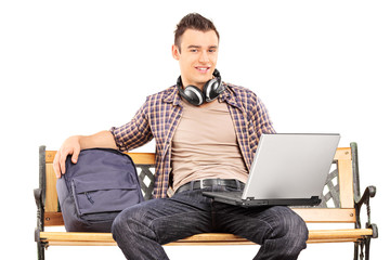 Young man with laptop sitting on a wooden bench