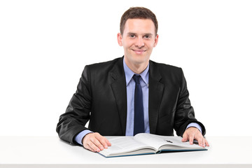Young businessman reading a book seated at a table