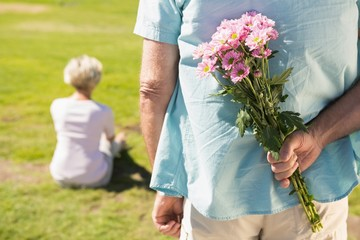 Senior man hiding flowers behind his back