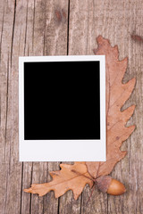 Instant film and autumn leaves on wooden background