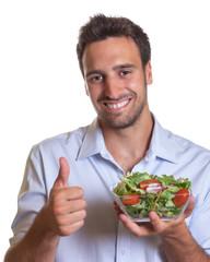 Lachender Mann empfiehlt frischen Salat