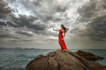 Woman in red dress stands on a cliff with a beautiful sea view a