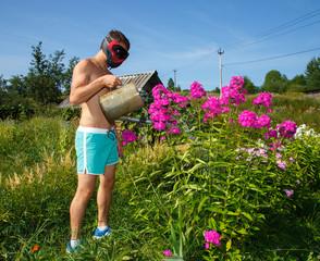 Brutal funny man in helmet watering flowers
