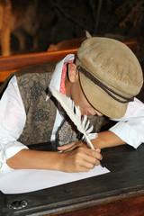 enfant écrivant à la plume