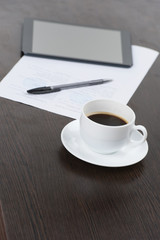 Tablet computer with cup of coffee and pen at table.