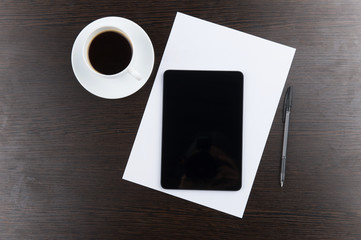 top view of tablet computer with cup of coffee and pen at table