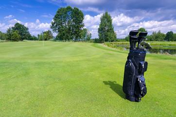 Golf bag on a green field