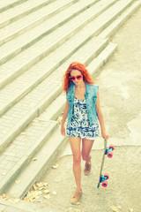 Beautiful redhead young woman walk a skateboard