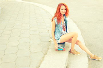 Red haired girl sitting on  her scateboard.