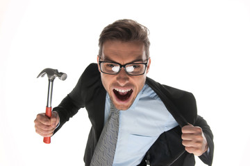 Angry businessman about to hammer on white background.