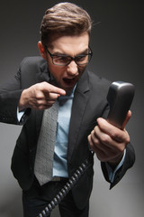 Angry businessman yelling into landline phone on white.
