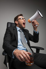 Young businessman shouting and sitting on chair.