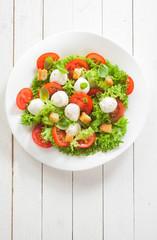 Caprese salad with mozzarella pearls and tomato