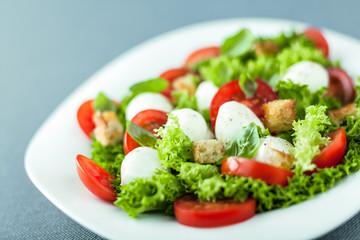 Serving of fresh salad with mozzarella pearls