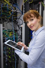 Smiling technician using tablet pc while analysing server