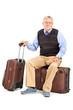 Senior man sitting on his baggage
