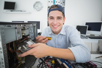 Smiling computer engineer working on console