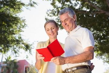 Happy senior couple using the guidebook