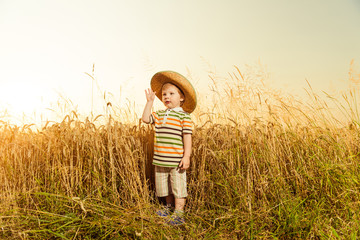boy in hat at farm wheat field sunset