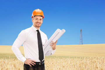 Male engineer holding construction plans In a field