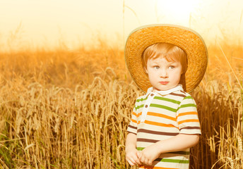 cute funny boy in hat at farm wheat