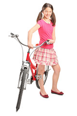 Teenage girl standing by a bicycle