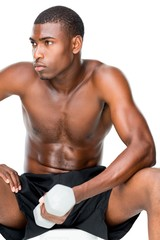 Determined fit shirtless young man lifting dumbbell