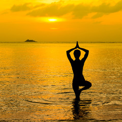 Yoga women silhouette, working on poses at sunset