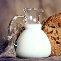 jug with milk and whole grain bread