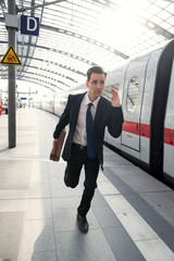 Businessman running after the train