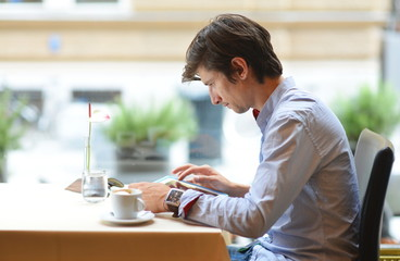 Young fashion man / hipster drinking coffee with tablet computer