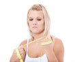 Upset young woman holding measuring tape
