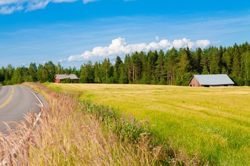 red farm with the road, blue sky and green field