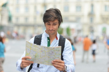 Young tourist watching the map in the city center