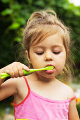 Summer portrait of adorable  little girl brushing teeth