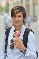 Portrait of handsome young man eating ice cream on the street