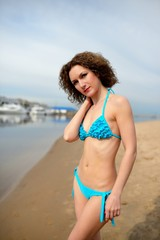 Beautiful girl with a curly hair in a blue bikini on a beach